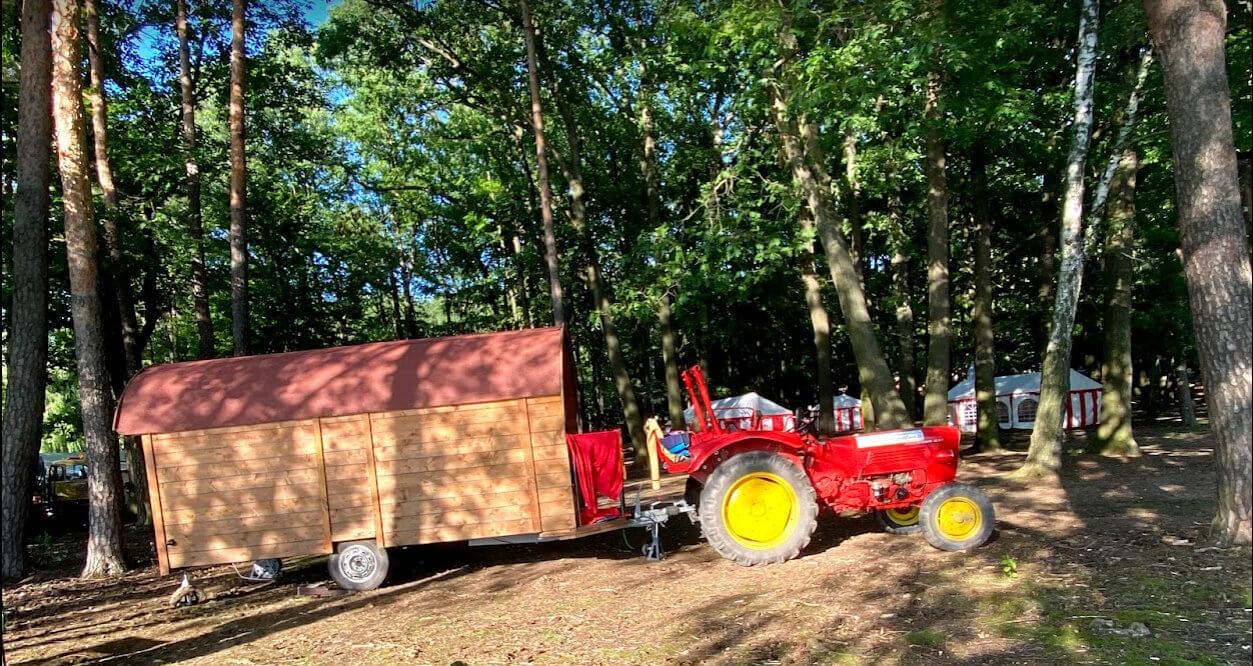 Traktor mit Wohnwagen im Wald